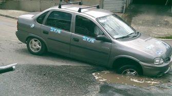 Carro cai e fica encalhado em um buraco em rua de Itaquaquecetuba